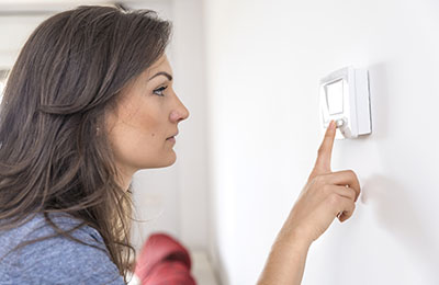 Woman setting thermostat in home