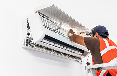 Technician repairing air conditioning unit in home